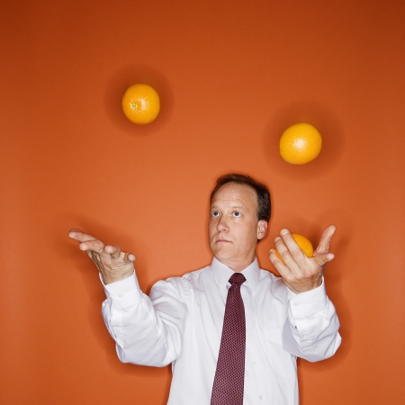 Caucasian middle aged businessman juggling oranges. photo