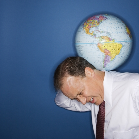 businessman carrying a globe: Caucasian middle aged businessman carrying world on shoulders straining. Stock Photo