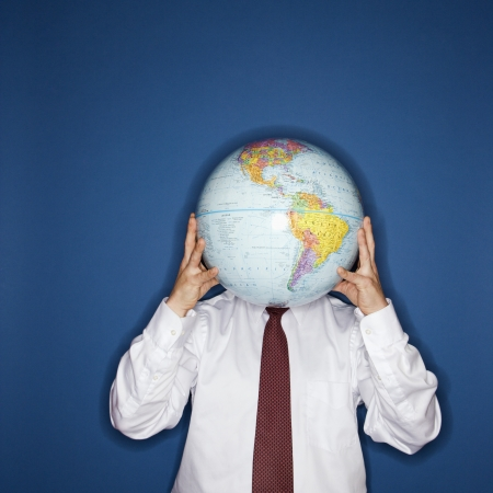 Caucasian middle aged businessman holding world globe in front of face. Stock Photo - 6924771