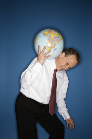 Caucasian middle aged businessman carrying weight of the world on his shoulders. photo