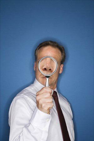 Caucasian middle aged businessman looking through magnifying glass. Stock Photo - 6924740