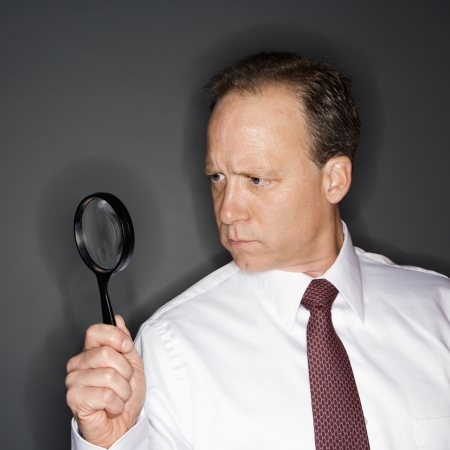 Caucasian middle aged businessman looking through magnifying glass. Stock Photo - 6924761