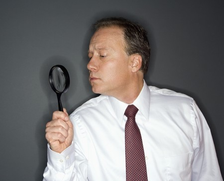 Caucasian middle aged businessman looking through magnifying glass. Stock Photo - 6924760