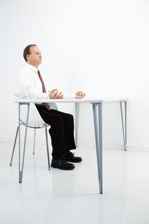 Caucasian middle aged businessman sitting at desk meditating. Stock Photo - 6924683