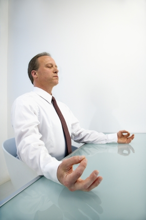 Caucasian middle aged businessman sitting at desk in meditation. photo