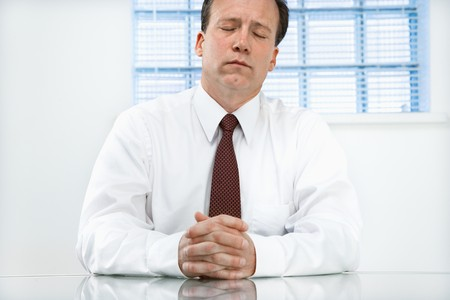 Caucasian middle aged businessman sitting at desk with eyes closed. Stock Photo - 6924692