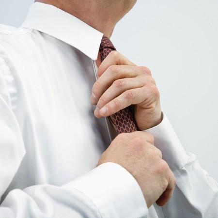 Caucasian middle aged businessman fixing necktie. photo
