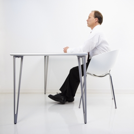 man side view: Caucasian middle aged businessman sitting at desk in office.