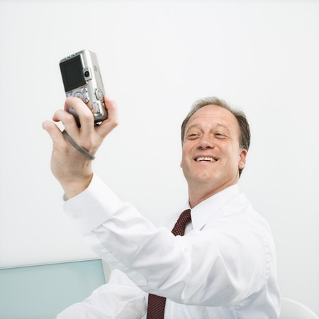 Caucasian middle aged businessman taking picture of himself with camera smiling. Stock Photo - 6924669