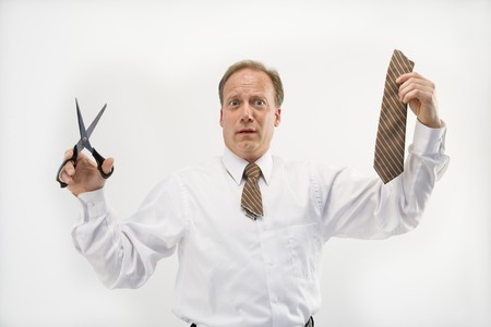 Caucasian middle aged businessman holding cut off necktie and scissors. Stock Photo - 6924676