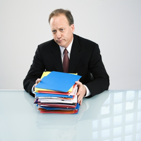 Caucasian middle aged businessman with stack of folders. photo