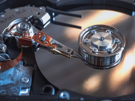 The old IDE hard disk internal components with a beautiful shiny magnetic disk.