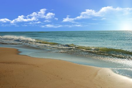 Morning seaside with gold sand and blue sky photo