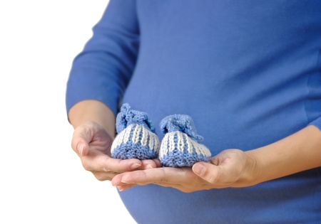 Pregnant woman holding baby booties. Focus on booties Stock Photo - 10920639