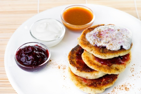 Fritters of cottage cheese with a jam and cour cream
