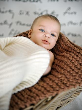 Newborn baby in a basket Stock Photo