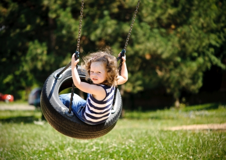 frolic: Little girl is swinging in a park