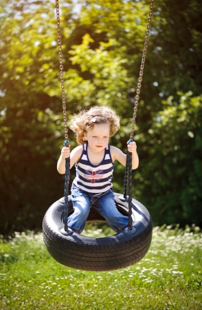 Little girl is swinging in a park photo