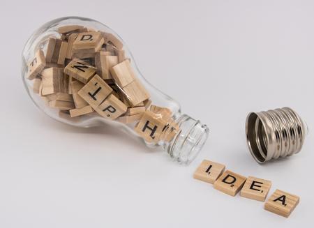 """Een gloeilamp, met een losgeschroefde socket, gevuld met lettertegels, spugen het woord """"idee"""" op een witte achtergrond."""