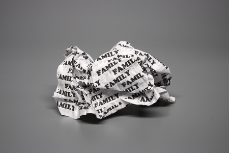 incest: A crumpled paper with the words family written all over it on a gray background.