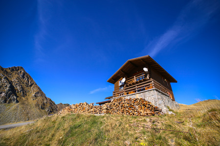 Autumn landscape with wood pile in front of cabin and Fagaras mountains in the background at the Balea Lake, in Sibiu county, Romania