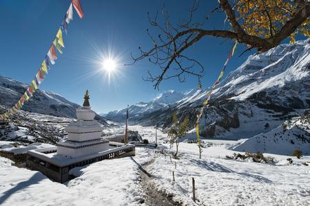 Buddhist Stupa in Nepal, blue sky, sunlight and prayer flags