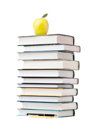 A yellow apple on a stack of books, isolated on white background