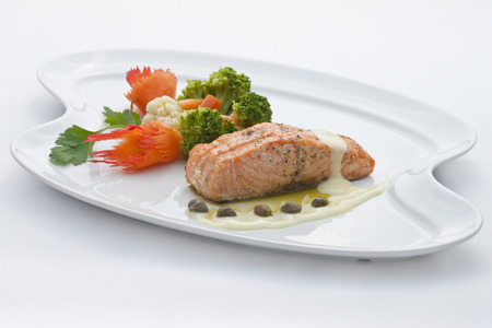 Atlantic salmon garnished with carrots, broccoli, capers and cauliflower Stock Photo