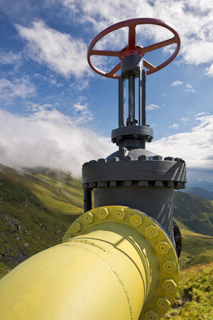 Yellow gas pipe line valves with mountains background and blue sky with clouds Stock Photo
