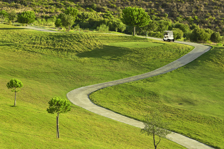 Golf course during sunrise with golf car Stock Photo