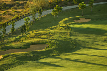 Sand bunkers on the green golf course at sunrise Stock Photo