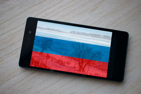 bandera de rusia: black smart phone close-up with Russia flag wallpaper on wood background