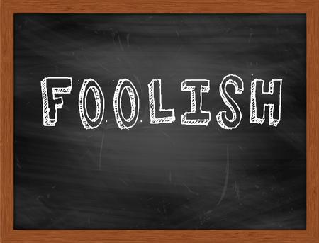 foolish: FOOLISH  hand writing text on black chalkboard Stock Photo
