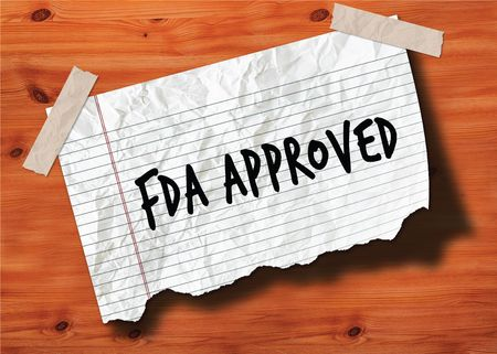 FDA APPROVED handwritten on torn notebook page crumpled paper on wood texture background. Illustration Stock Photo
