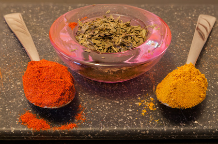 a jar stand: Curry and paprika in spoons and tarragon in a jar,isolated on a kitchen stand