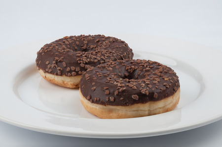rin: Two chocolate glazed rin donuts served on a white plate on white background