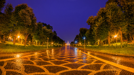 Alley with reflections in Carol Park in Bucharest during rain in a night