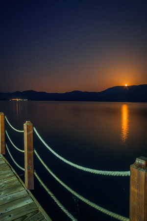 Beautiful moonrise during summer night over Danube river on a pontoon with a city in the background