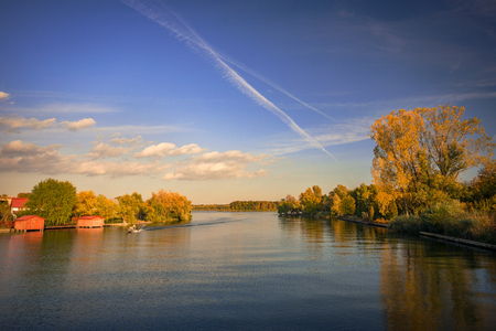 Boat passing on Snagov Lake in Romania near house and autumn colored forest