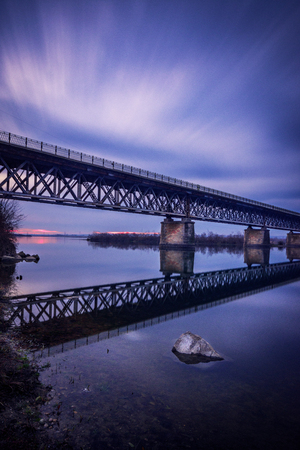 Cloudy day long exposure over a bridge on Olt river in Romania in late autumn 스톡 콘텐츠