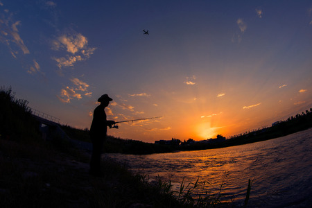 Fisherman silhouette at sunrise holding his rod with a plane flying above