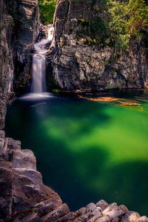 Beautiful waterfall falling through rocks and forming a deep lake on the Fonias river on Samothrace Island in Greece with leaves foliage moving on the surface Stok Fotoğraf