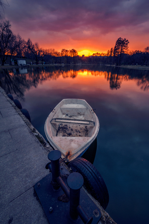 Sunset scene in a park in Bucharest with a boat in the foreground tied to the shore shot at the beginning of the spring