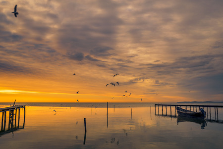 Lake scene in the morning at sunrise with birds flying above the lake and a boat near a pontoon shot in Romania Banco de Imagens