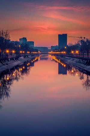 Lebendiges Stadtbild, aufgenommen am frühen Morgen vor Sonnenaufgang in Bukarest mit einem Fluss im Vordergrund und großen Gebäuden Standard-Bild