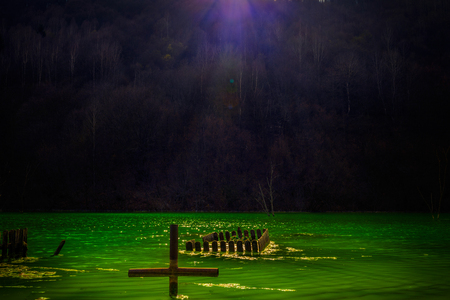 The remains of a graveyard located in a valley flooded with waste from a mining company with a cross being covered in polluted waters in Romania Stock Photo