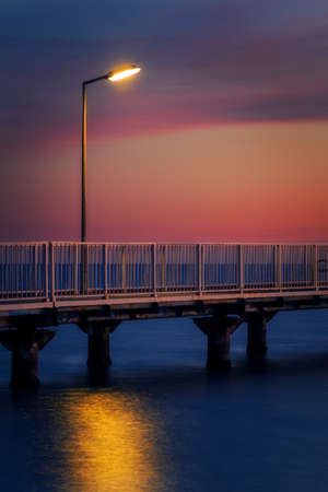Detail of a walking pontoon with a lamp post at the sea in the morning before sunrise