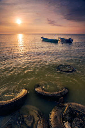 Beautiful sunrise or sunset on a lake with wooden fisherman boats on a cloudy morning with rubber tires in the foreground used as a pontoon 版權商用圖片