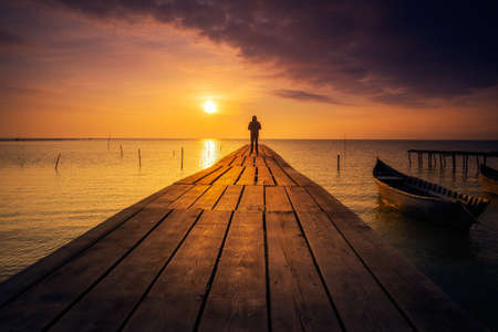 Lonely person standing on a pontoon meditating and enjoying the sunrise or sunset on a lake with a fishing boat on the lake 版權商用圖片