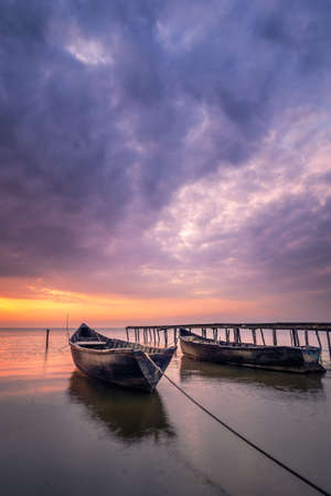 Beautiful sunrise or sunset on a lake with wooden fisherman boats on a cloudy morning
